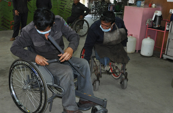 Two technicians from the Veteran's International wheelchair workshop try out the leveraged freedom chair and provide valuable feedback. Photo: Carolina Kaelin