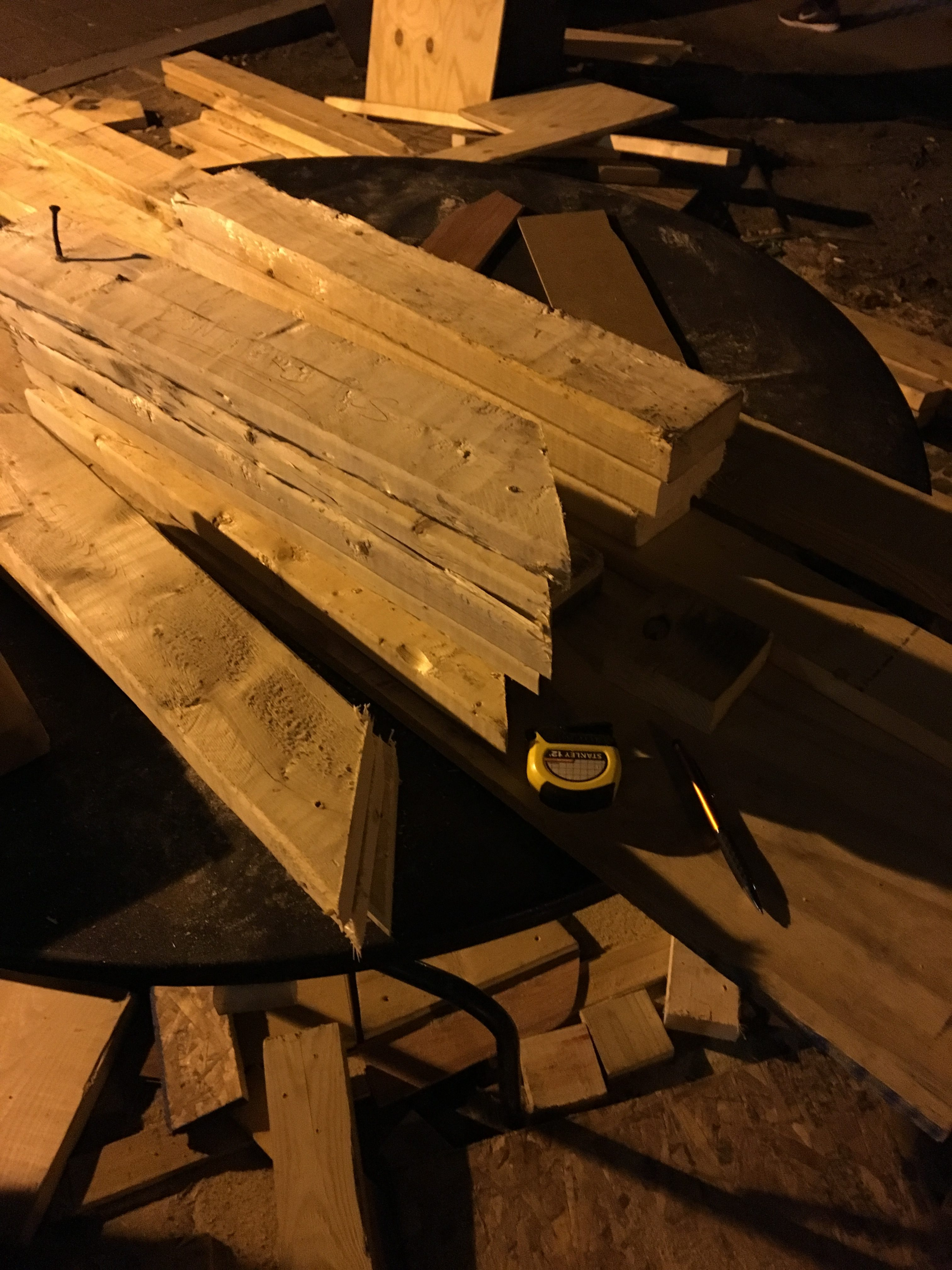 A pile of 2x4s with diagonally-cut edges on a table. The picture is dark.