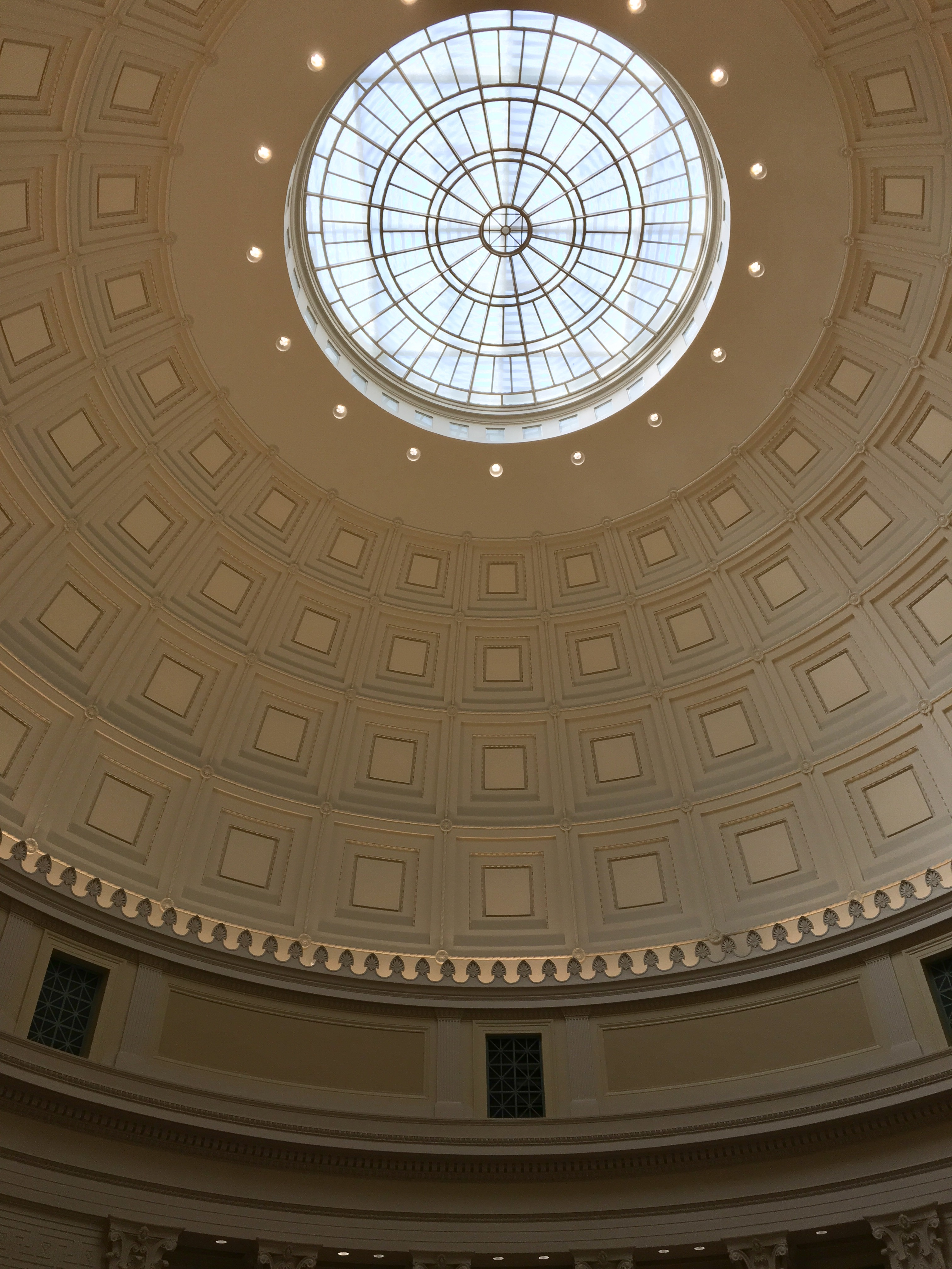 Looking up at the dome. Most of the image is taken up by concentric rings of beige squares; at the very top of the dome, there's a circular clear glass window through which bluish natural light can be seen.