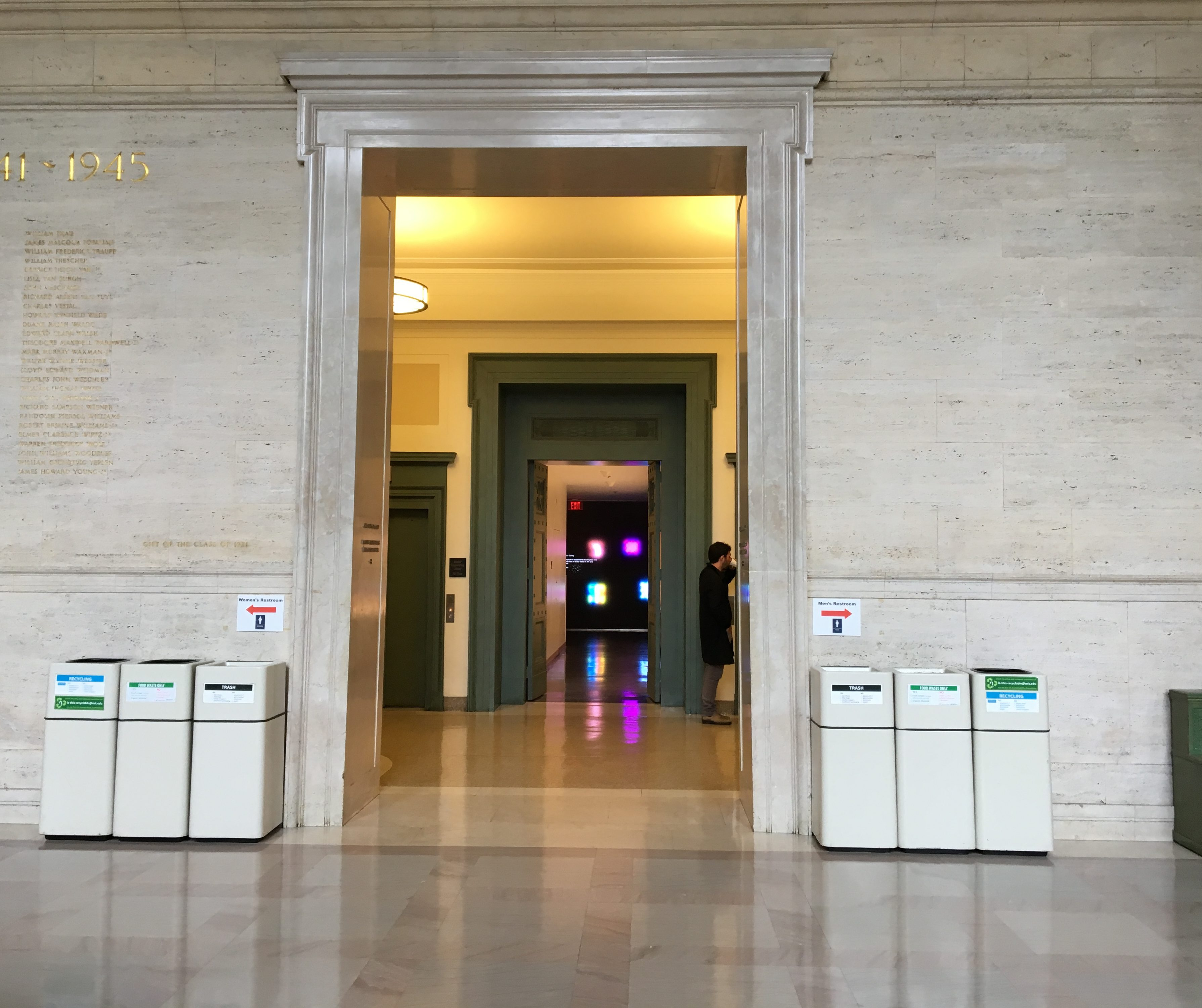 A marble wall with an enormous doorway in the middle of it. Through the doorway, another room can be seen, with a hint of a green elevator door and another green doorway.