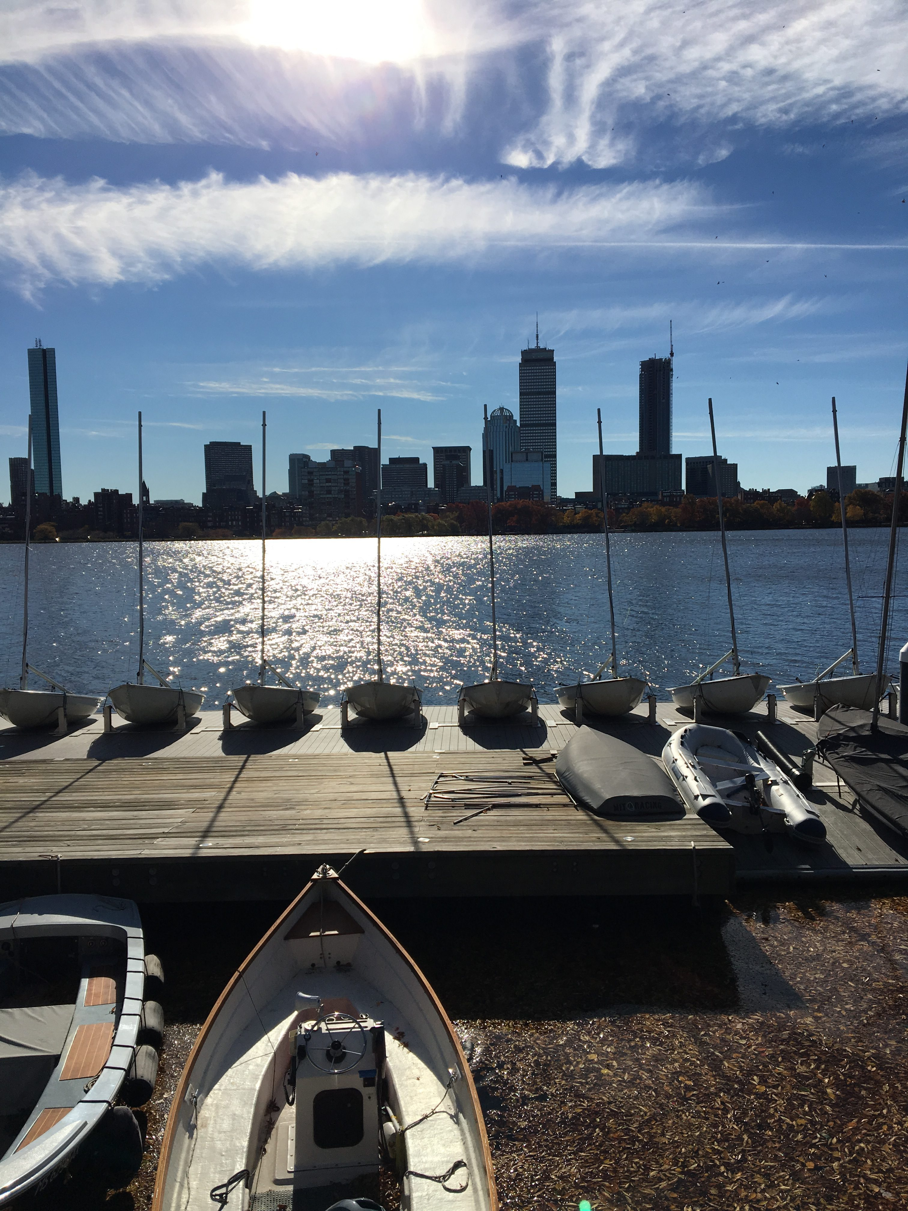 A view from next to the river. Docked rowboats are in the foreground, the blue river with sunlit ripples in the middleground, and the Boston skyline and fluffy clouds in the background.