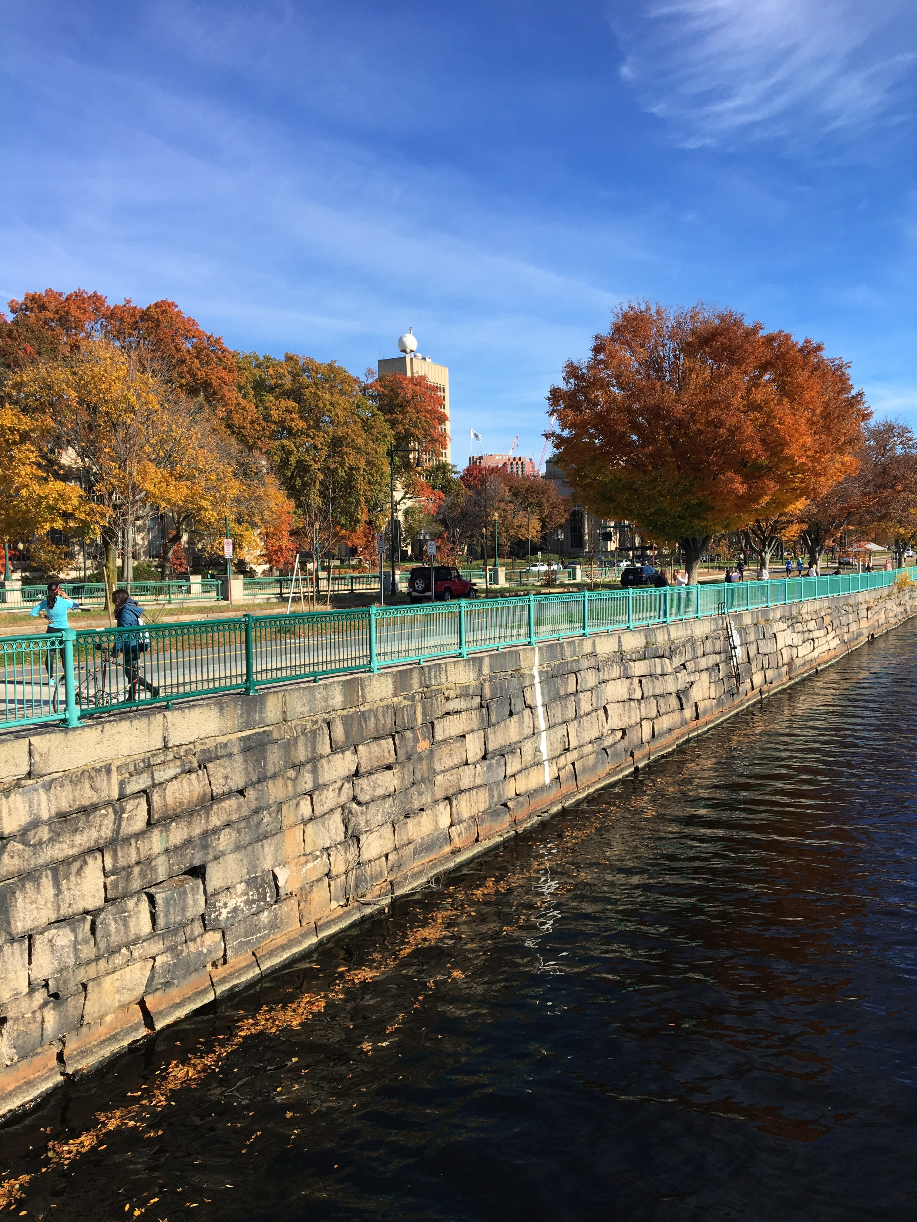 """A view right from the end of the """"Harvard"""" Bridge; the stone riverbank and teal railing are in the foreground, with dark orange trees behind them."""