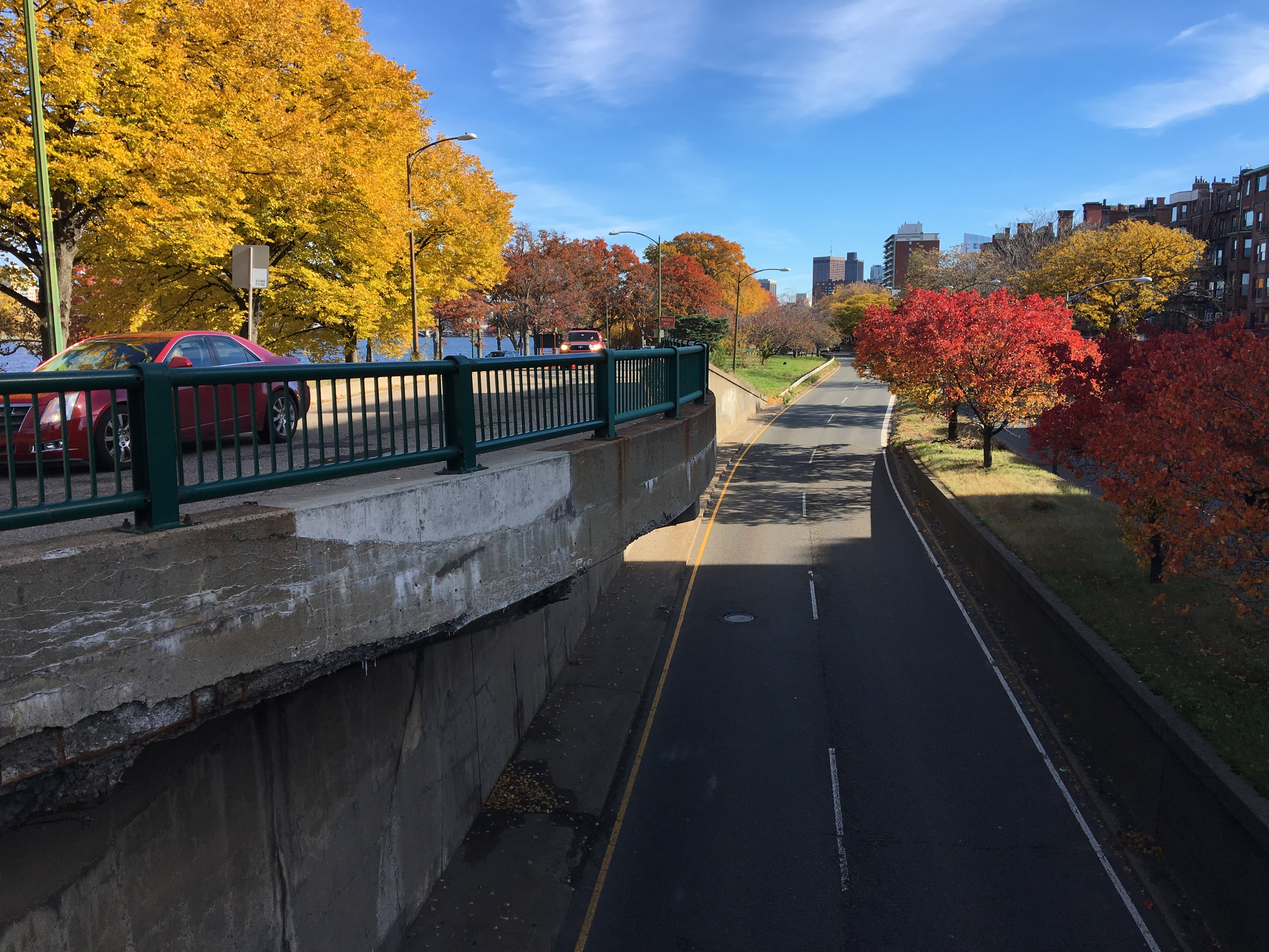An overpass with yellow trees to the left and red trees to the right, with blue sky in the middle.
