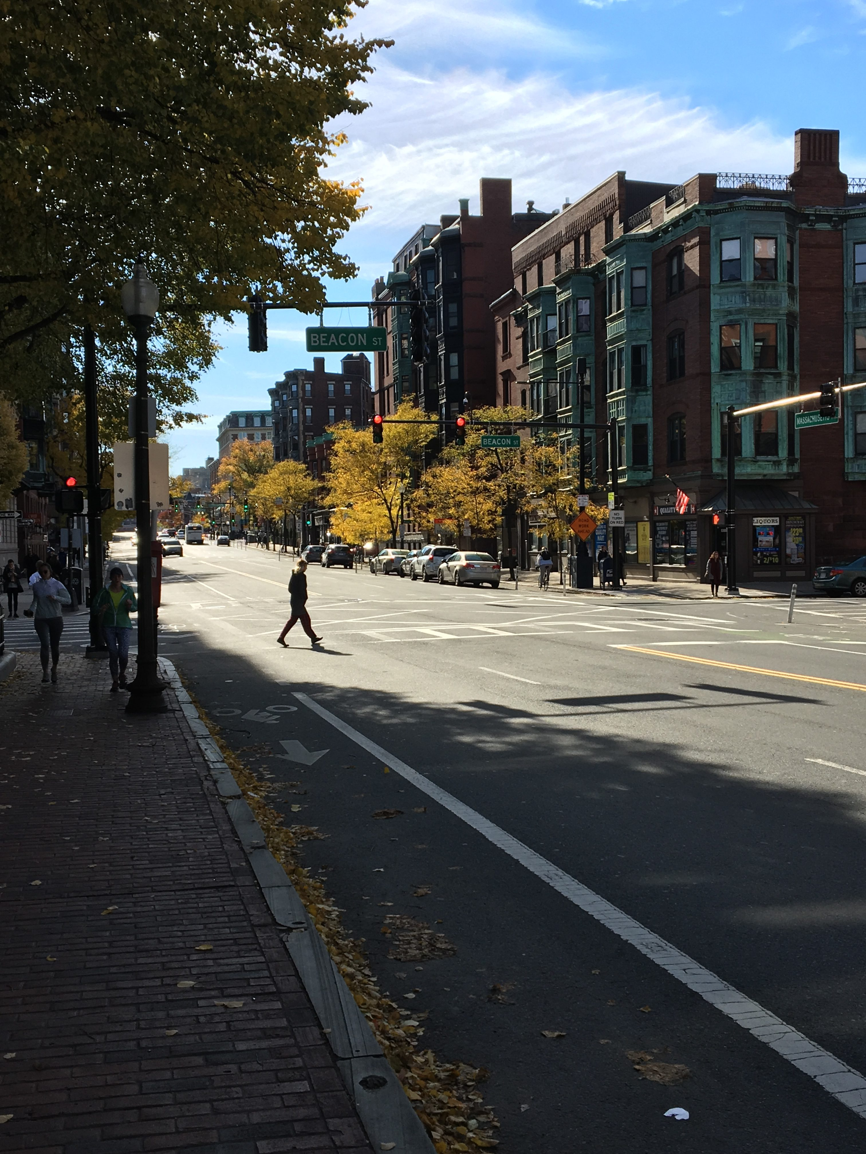 A road in Boston; red brick buildings are visible on the other side. The trees cast a shadow over the foreground but sunlight illuminates a man walking across the street in the middleground.