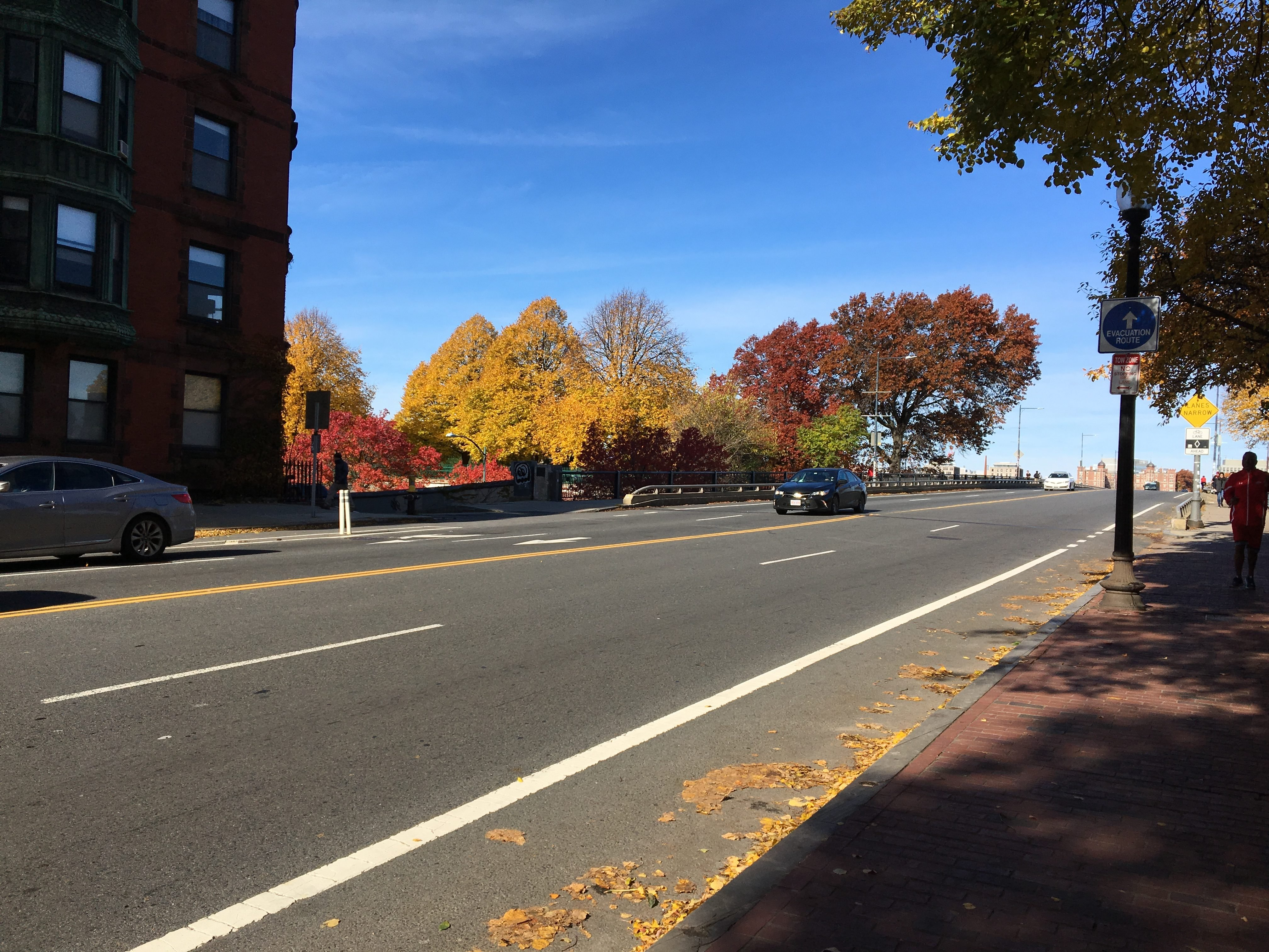 A road in Boston. Visible are part of a Boston-typical red brick building, a blue sky, and various brightly-coloured trees.