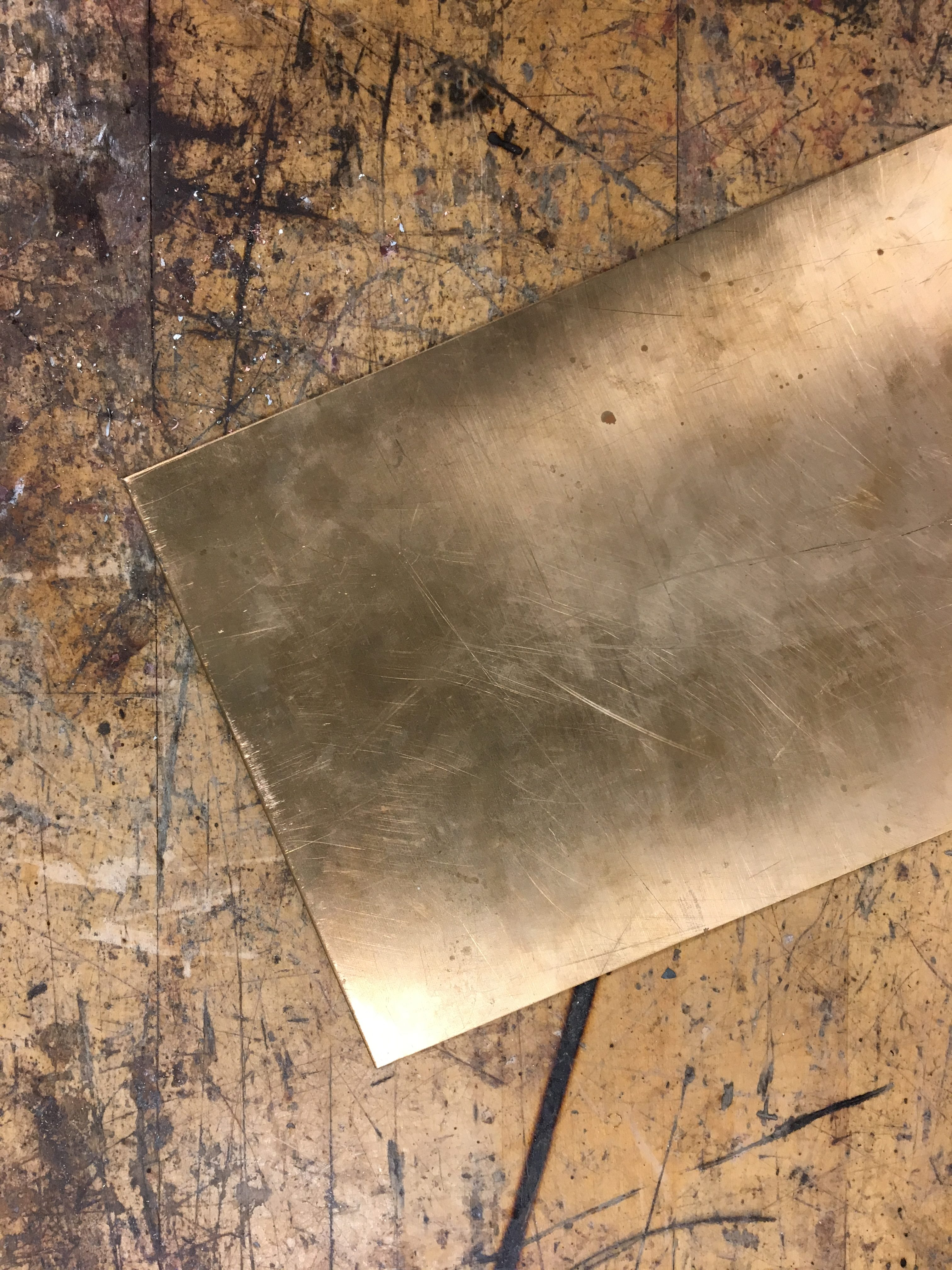 A plain, flat sheet of copper on a wooden table.