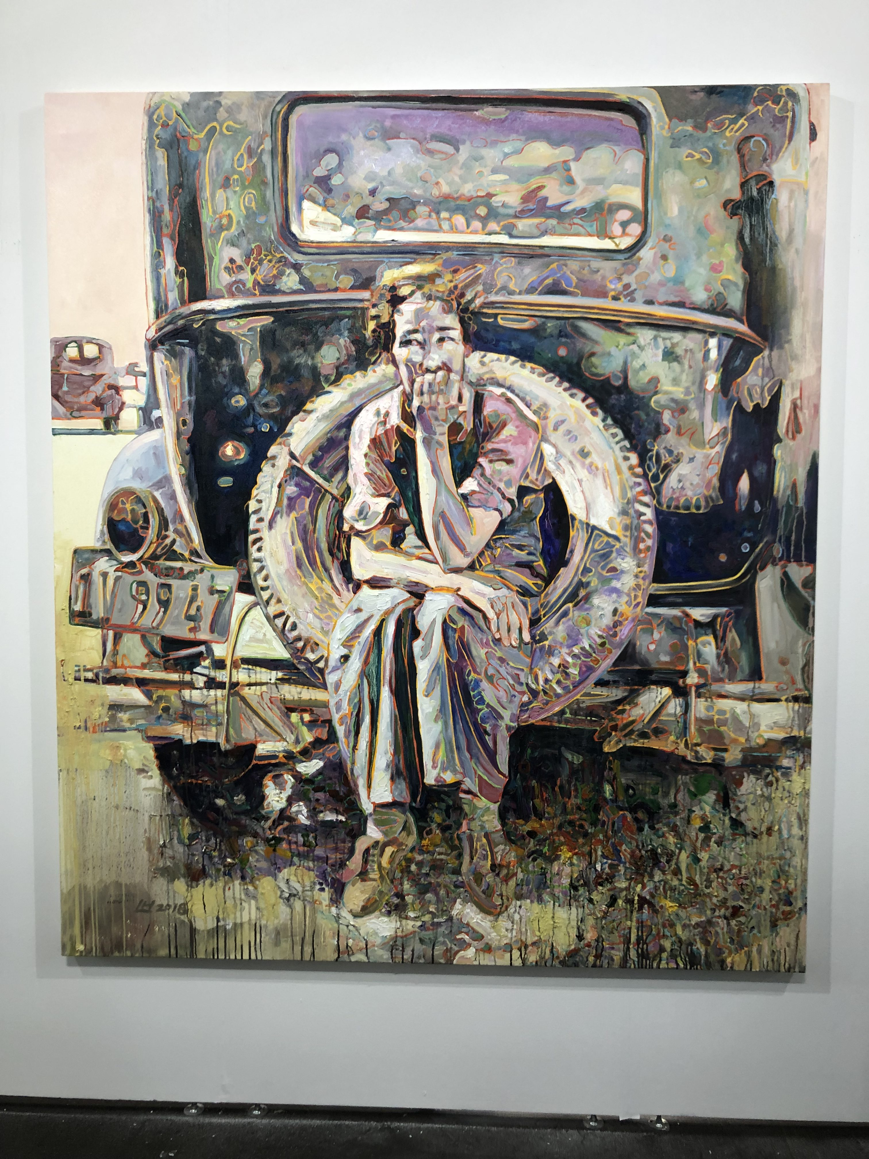 a painting of a person in thought sitting on the spare tire perched to the back of a car (painted very stylistically with many colors)