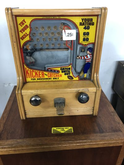 a vintage quarter game where a metal ball is kicked up from the bottom right corner, and then goes through prongs on the way down. To win the ball must be caught in the basket.