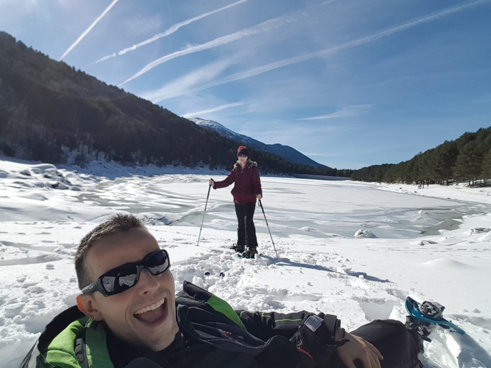 Showshoeing by an ice-covered lake with a beautiful blue sky!