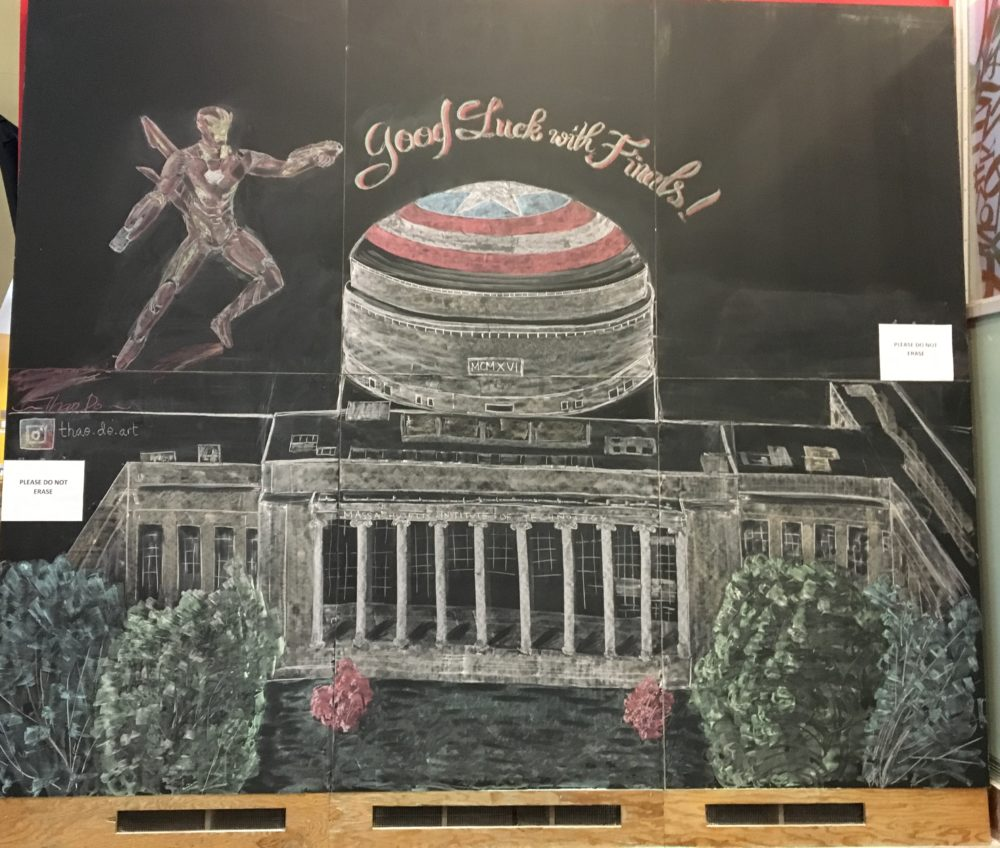 "A very large blackboard inside the Stata Center. It is a detailed drawing of MIT's Killian Court, lobby 10, and the big dome. The dome is covered in Captain America's shield. Above it, Iron Man flies next to the words ""Good Luck with Finals!"""