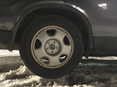 the back wheel of a car perched on a narrow strip of snow