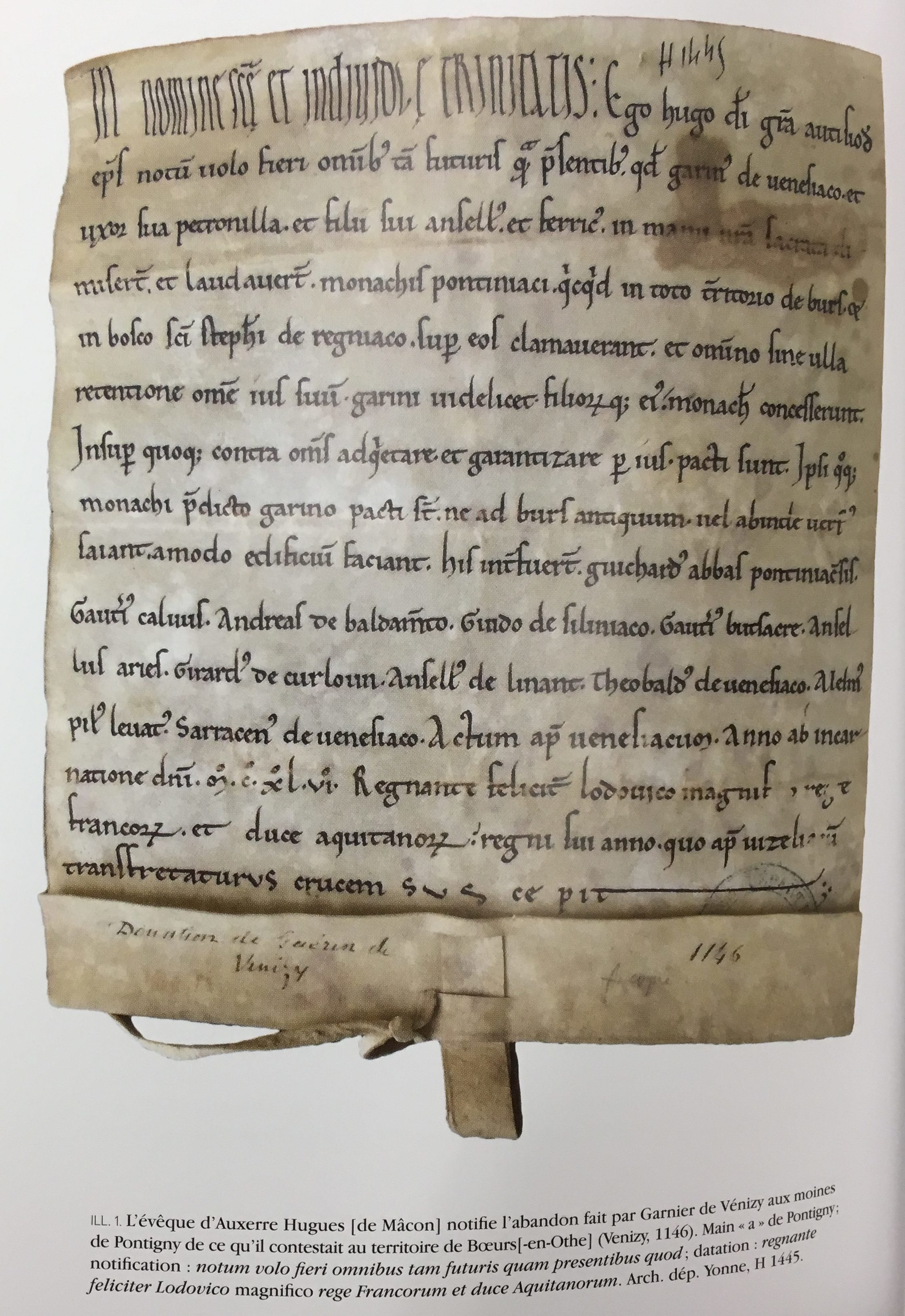 A piece of vellum with ornate medieval Latin script inked on it.