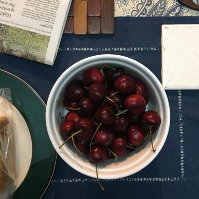 An aesthetically-framed photo of a bowl of cherries on a dining room table.