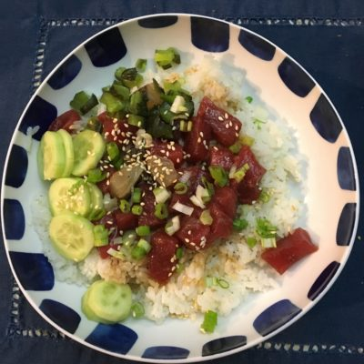 An aesthetically framed bowl of poke (rice, tuna, scallion, cucumber, sesame seeds).