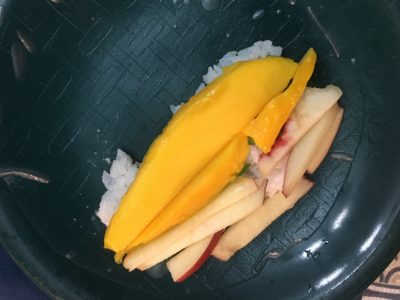 An unfinished summer roll. The mango and apple are laid on top of rice, all on top of an unrolled rice paper circle.