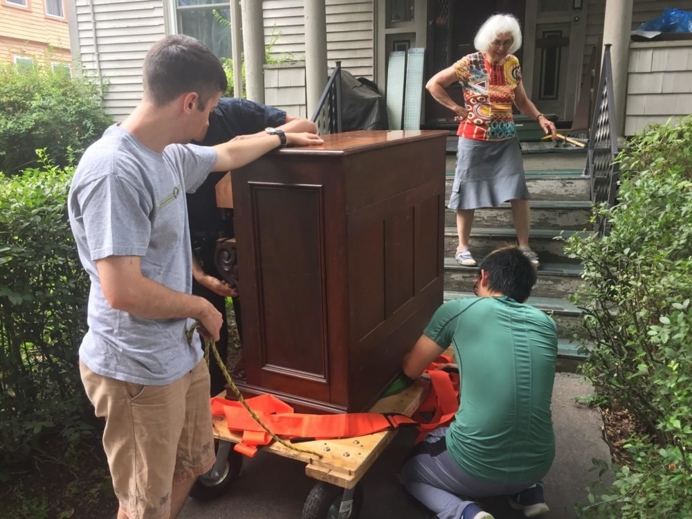 three people strapping down organ