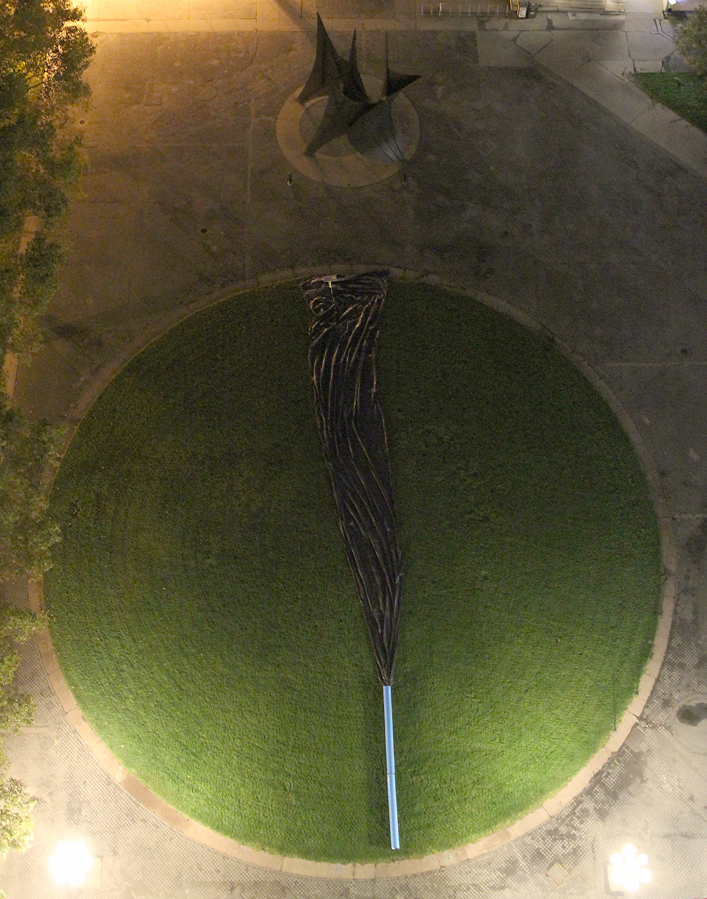 A picture from high above the dot (McDermott Court). At the bottom of the dot is a blue pipe, reminiscent of those in Futurity Island; from it comes a giant black tarp, mimicking an oil spill.