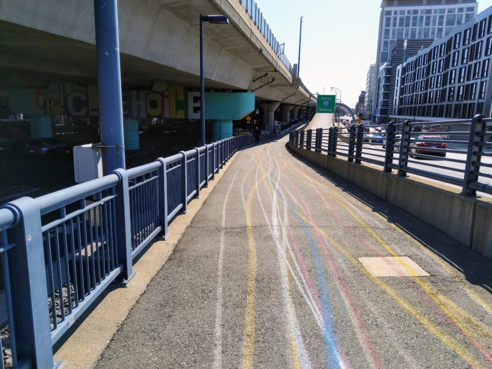 colorful lines appear on the sidewalk, as if drawn with chalk. they stretch to the horizon.