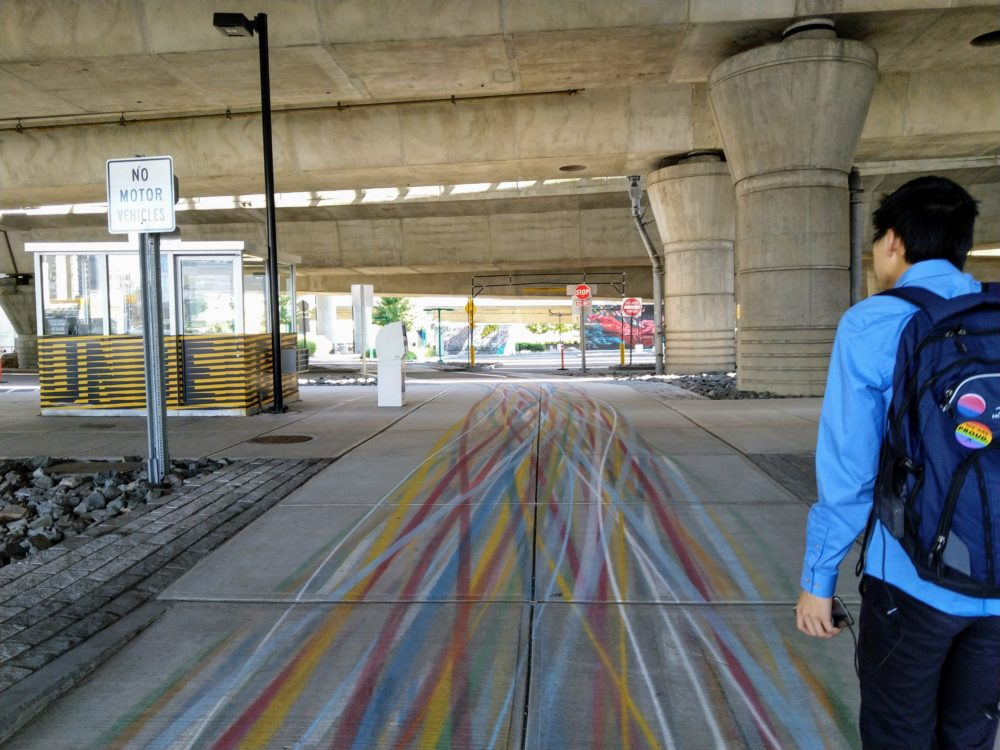 more colorful lines weaving into each other as the sidewalk widens to a path under the highway.