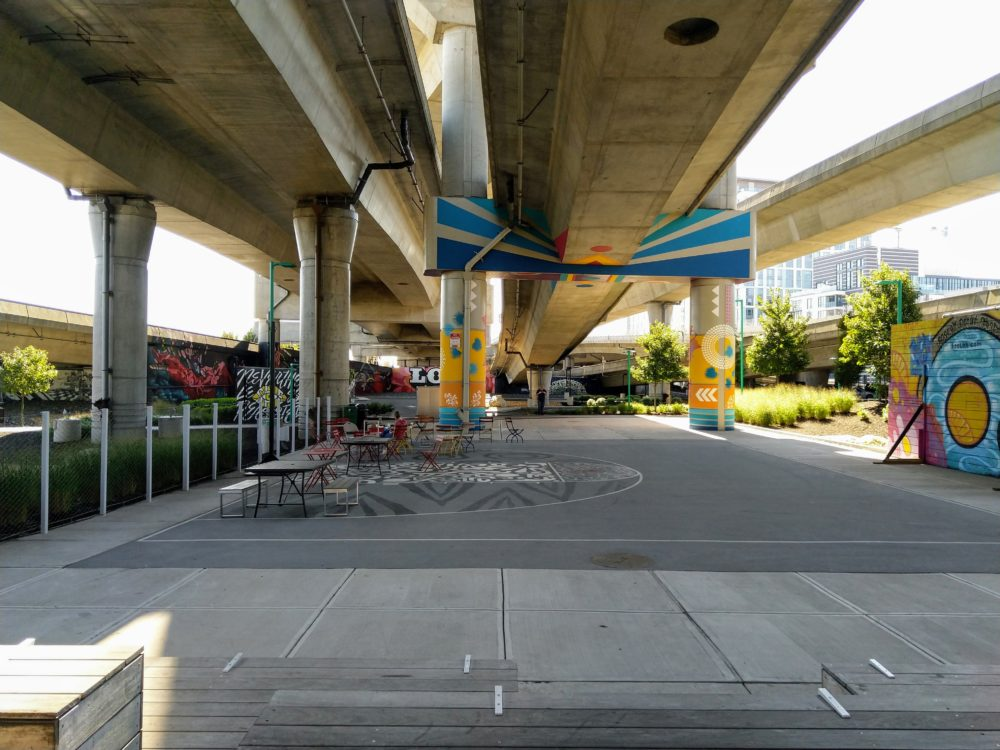 underneath the highway. there are some more murals, some chairs and tables too.
