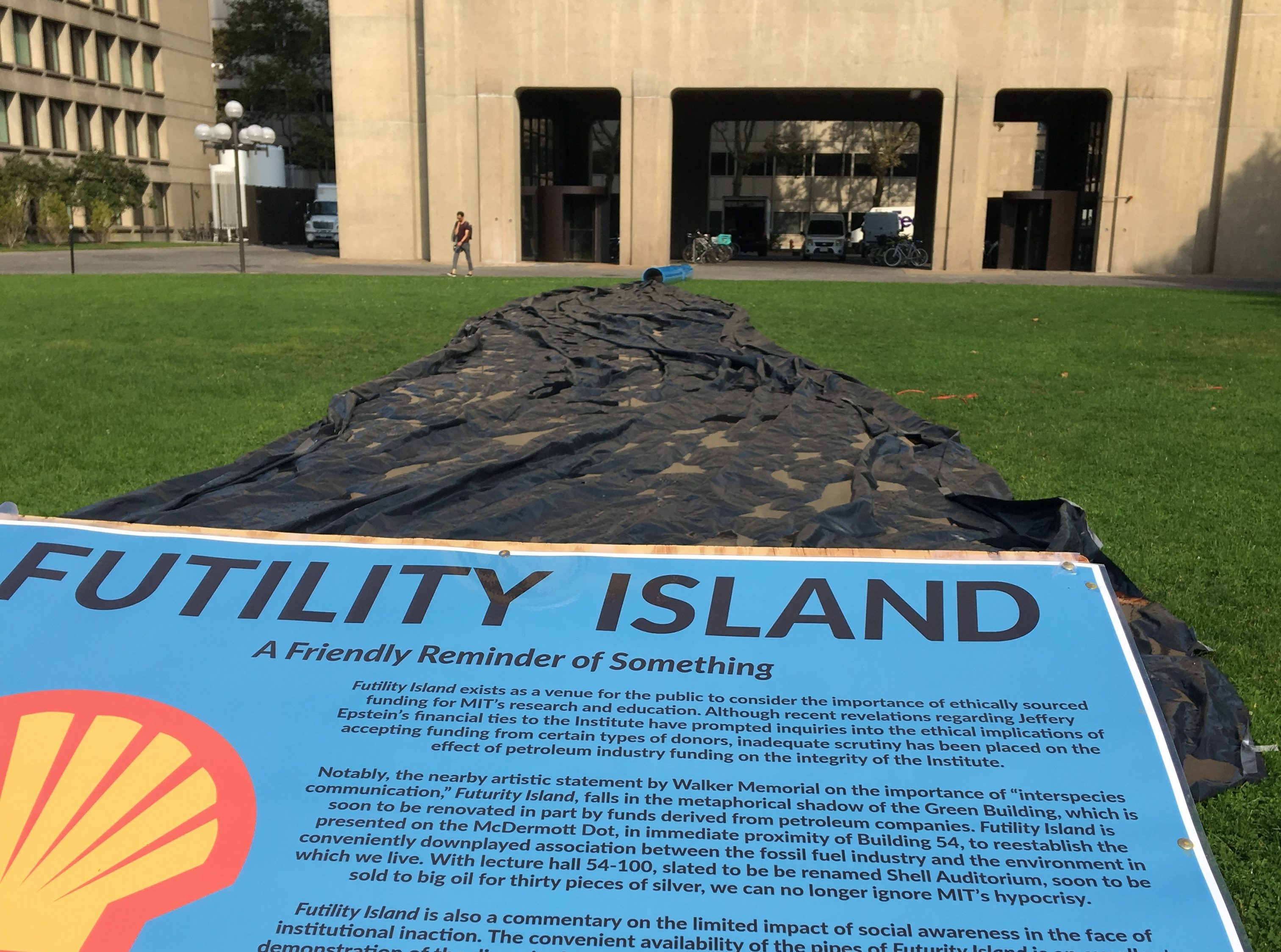 "A view of the hack from the sign describing it: the sign is in the foreground, and the black ""oil spill"" tarp stretches away into the blue pipe in the background. The Green Building can be seen behind the pipe."