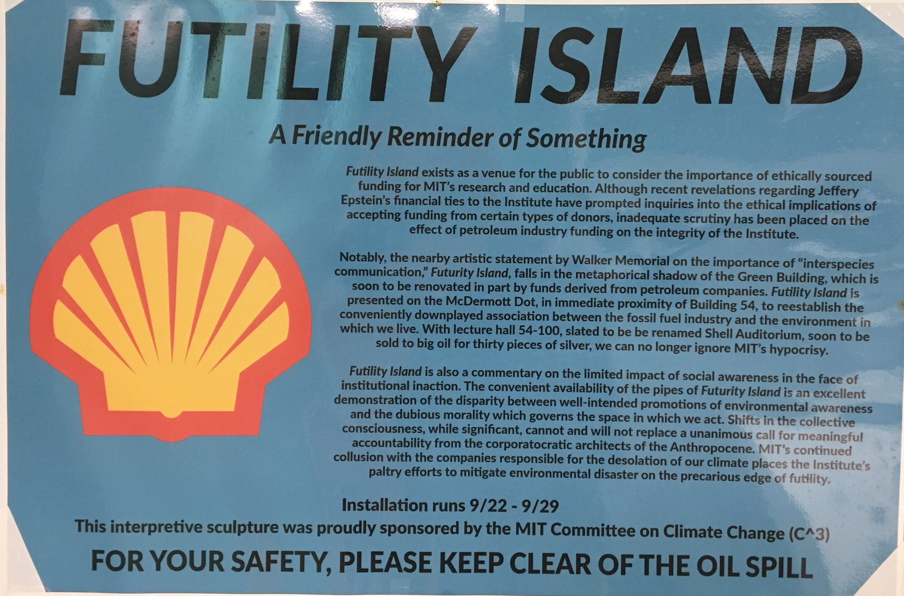 "A picture of the sign in front of the hack. It says ""FUTILITY ISLAND: A Friendly Reminder of Something"" and has text describing Futurity Island, the Green Building renovation, and denouncing MIT's ""continued collusion"" with polluting companies."