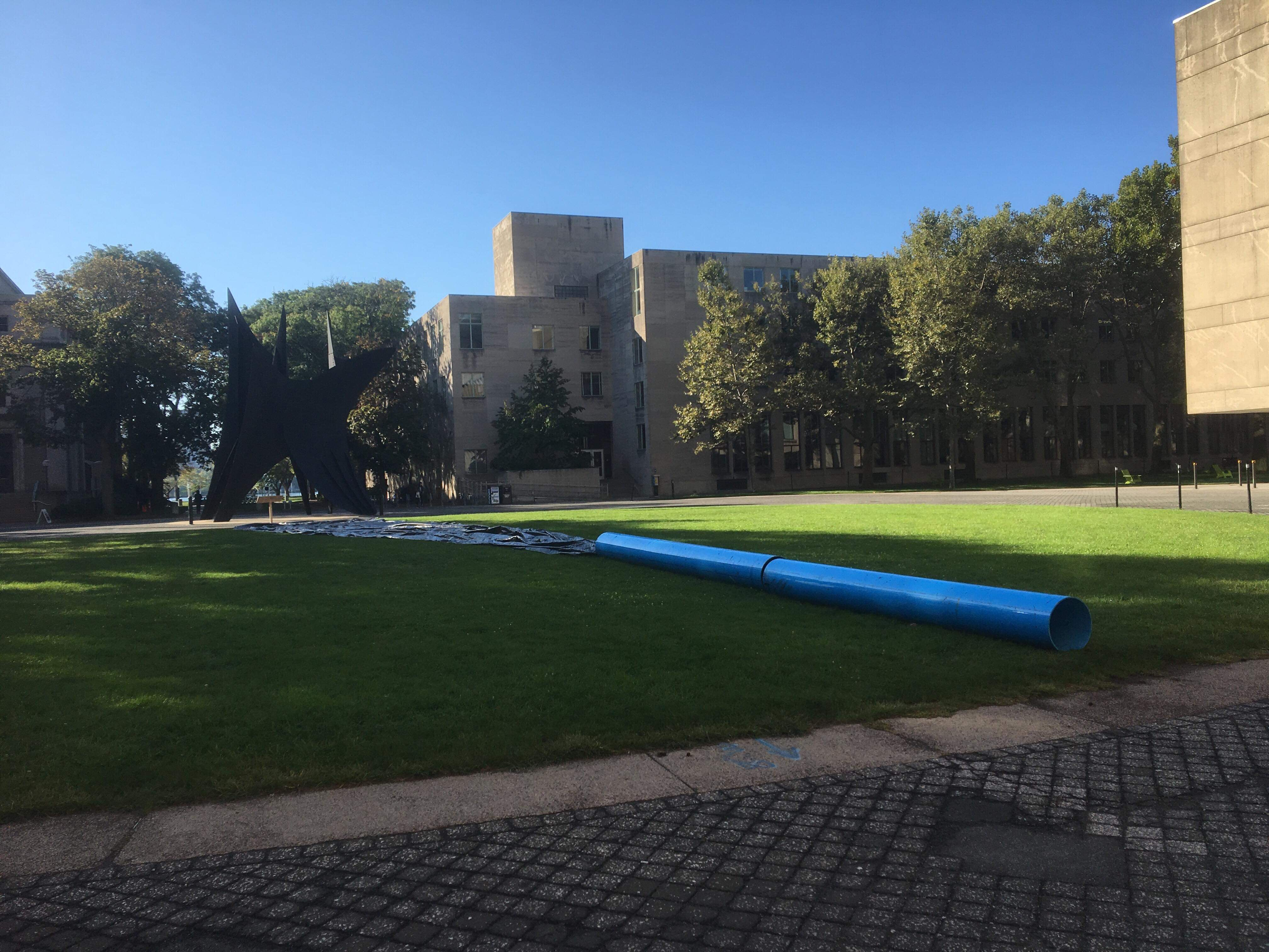 The hack from the ground. The photo is taken next to the large, bright blue pipe. Streaming away from it into the background is the black tarp.