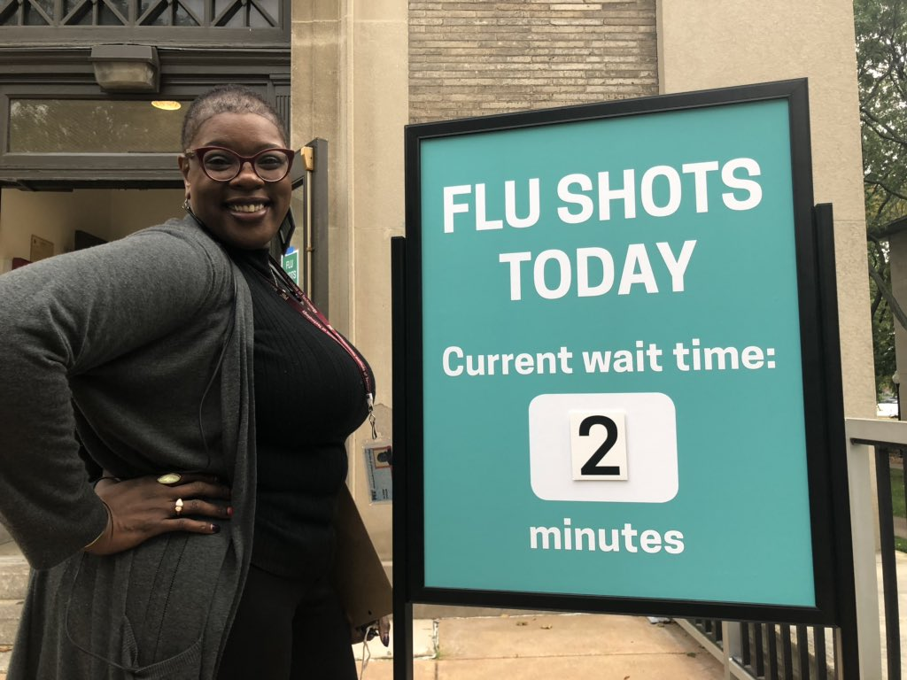 "one of mit medical staff stands beside a sign saying ""flu shots today / current wait time: 2 minutes"""
