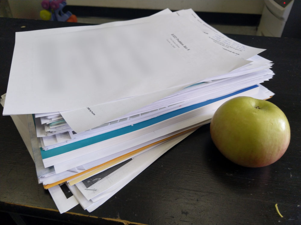 a stack of paper. next to it is an apple. the stack of paper is about twice as tall as the apple.