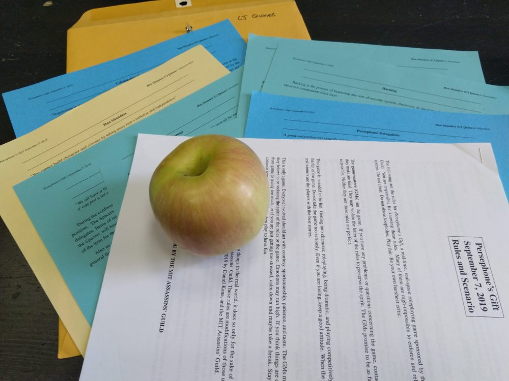 an apple lying on a stack of papers, and underneath is a folder