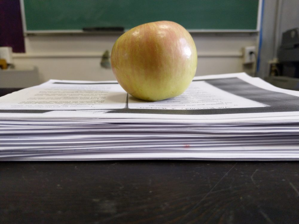 an apple on a stack of paper.