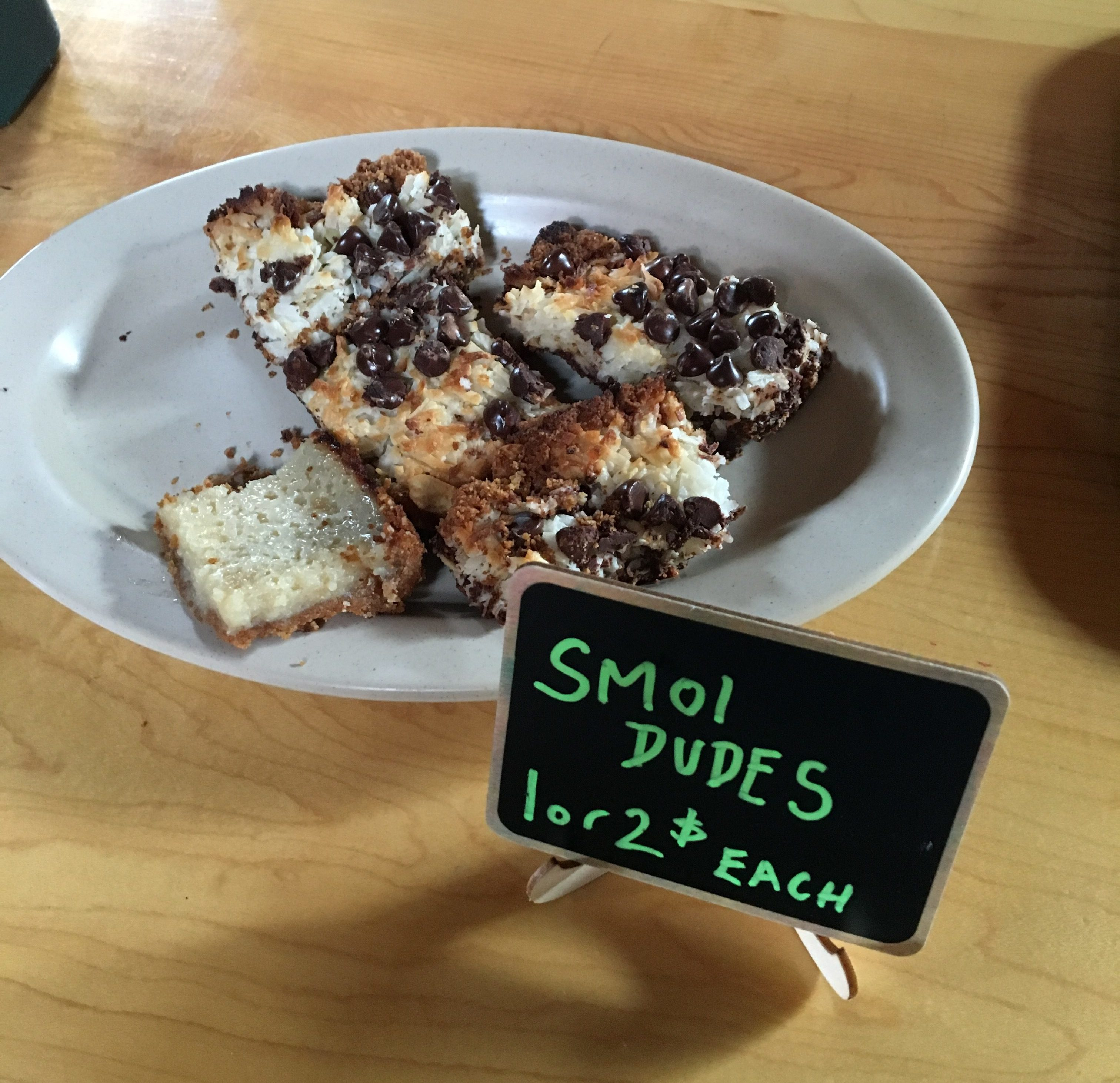 "A plate of brownies on sale in a restaurant. A small sign proclaims them ""SMOL DUDES: 1 or 2$ each""."