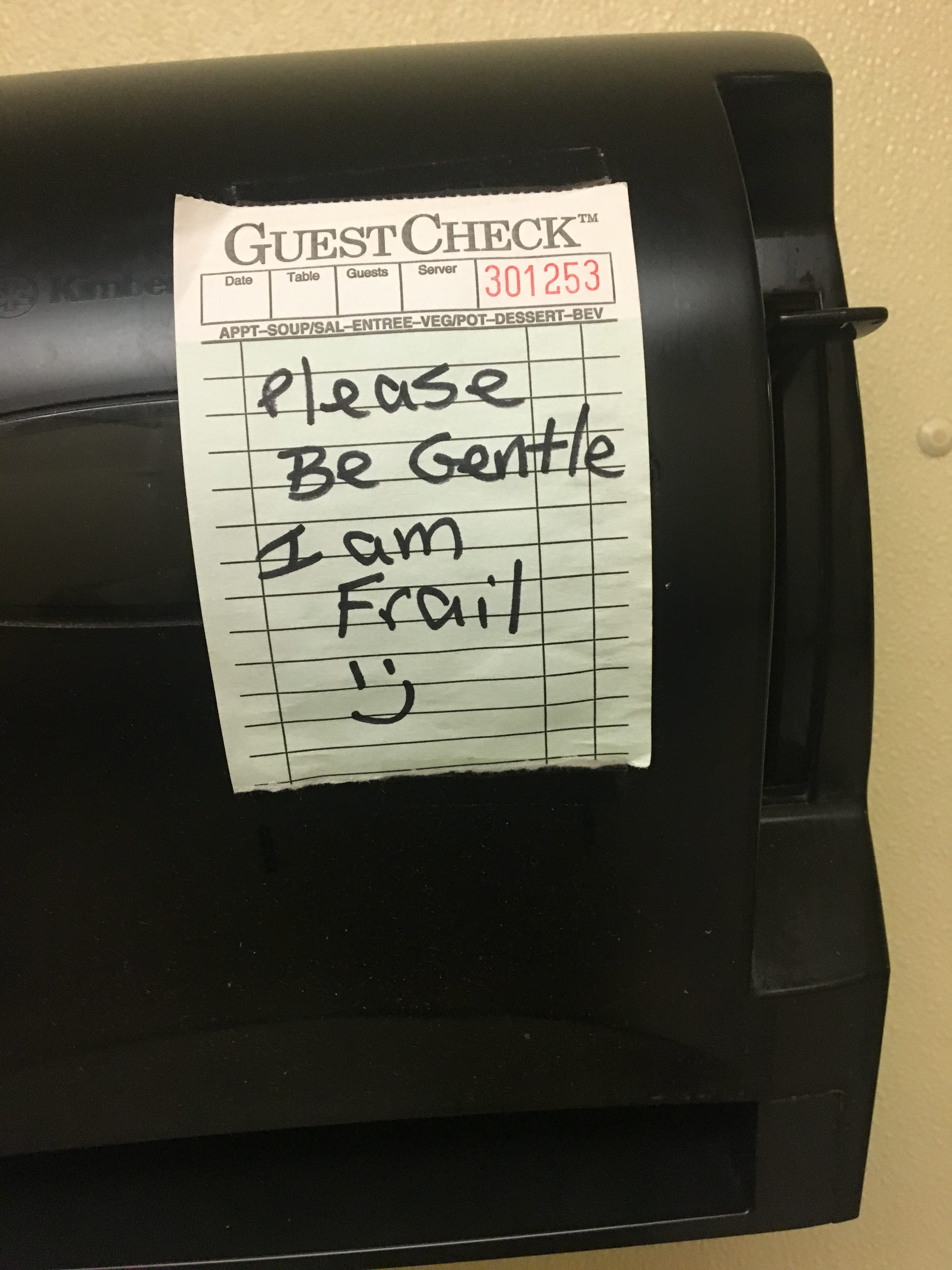 "A paper towel dispenser in a restaurant. A small sign on it reads ""Please Be Gentle I am Frail =)""."