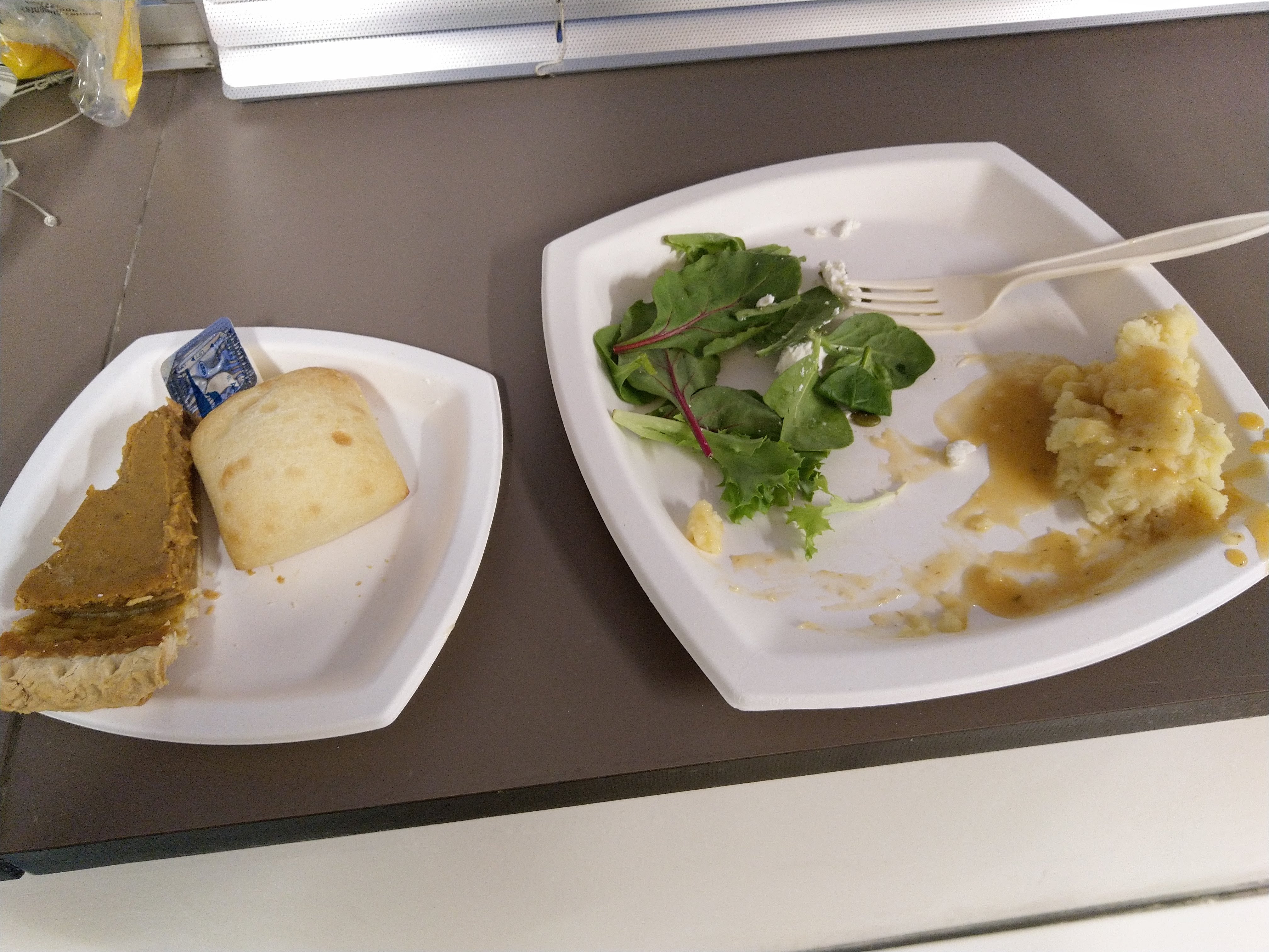 half-finished salad, mashed potato, pumpkin pie, and bread, and a fork, and butter, welp