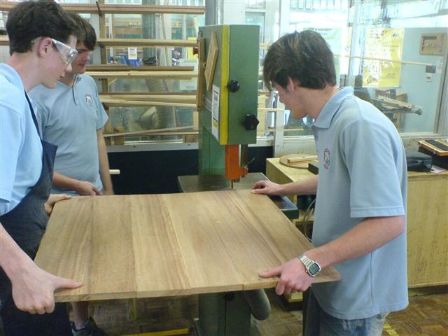 two people holding a large wood board and pushing it into a bandsaw