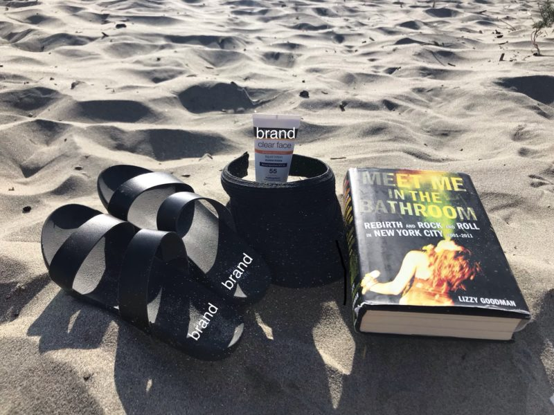 the book meet me in the bathroom lying on the sand at the beach
