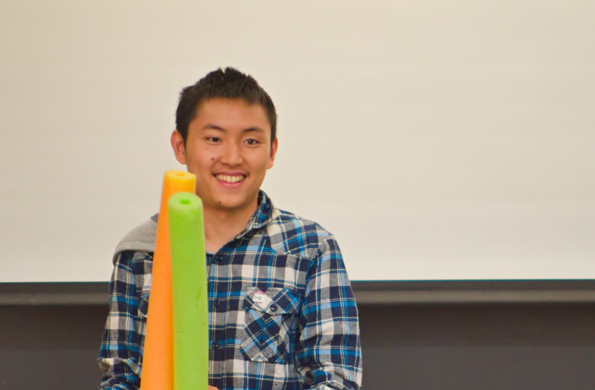 brian c. '19, holding pool noodles, and smiling. did you know he is always smiling