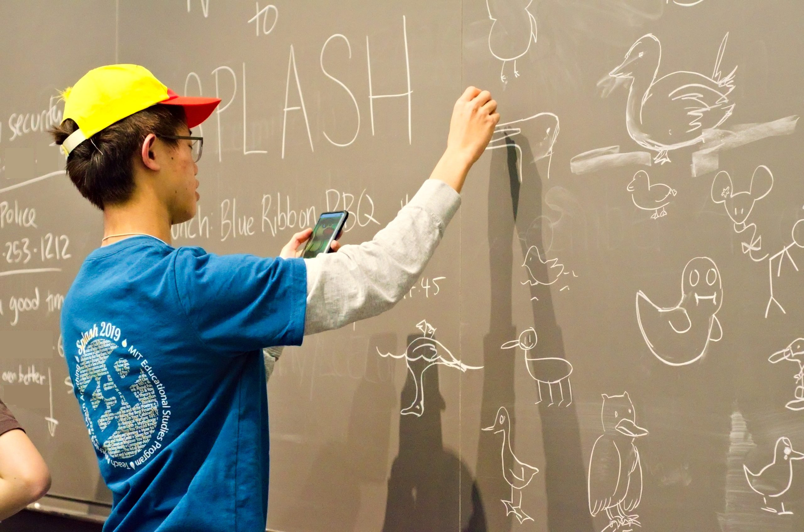 "vincent b. '23 drawing some ducks on a blackboard with around a dozen dash. ""SPLASH"" can be seen written on the background."