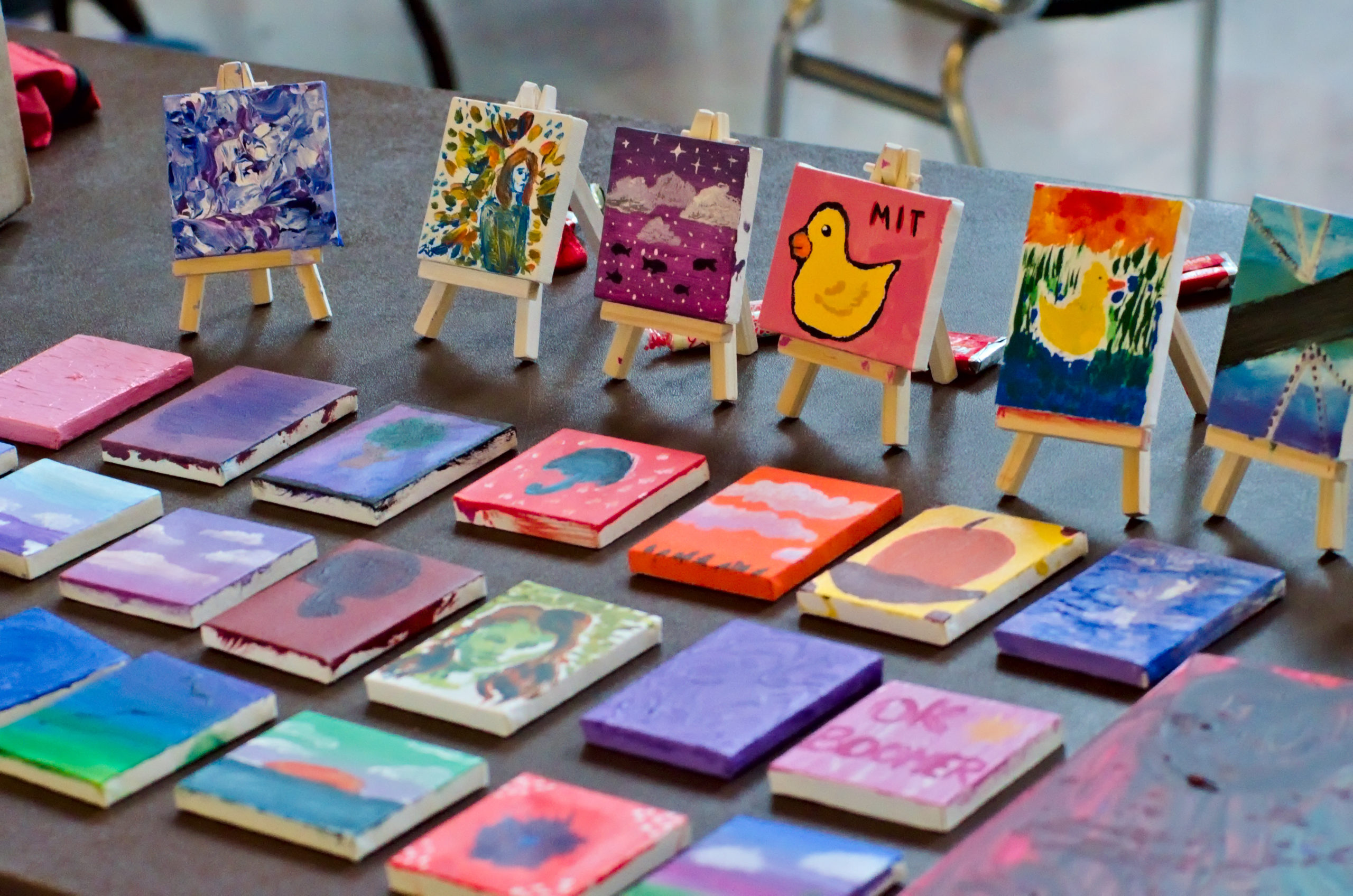 "several small (two inch square) paintings laid out on a table, some on tiny easels. notable paintings include a painting of a rubber duck, and one that says ""OK BOOMER"""