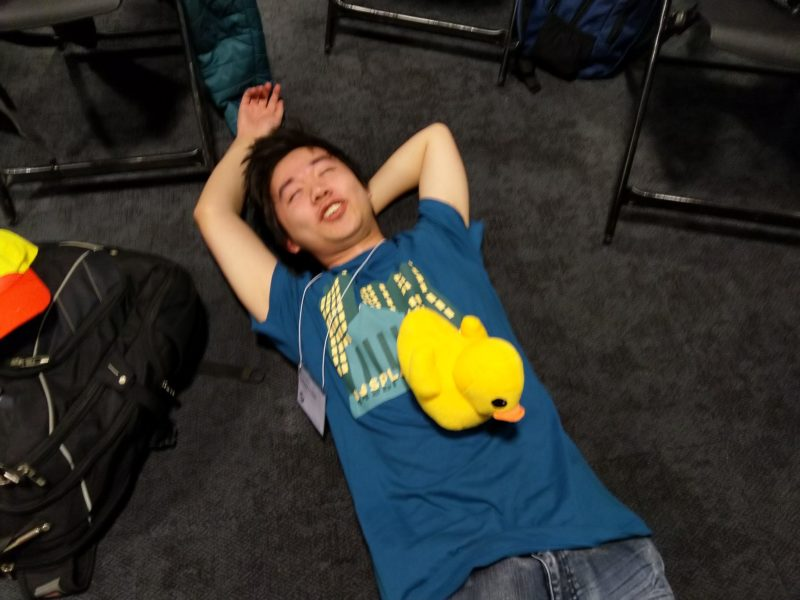 jeffery lying down on the floor with a duck on him