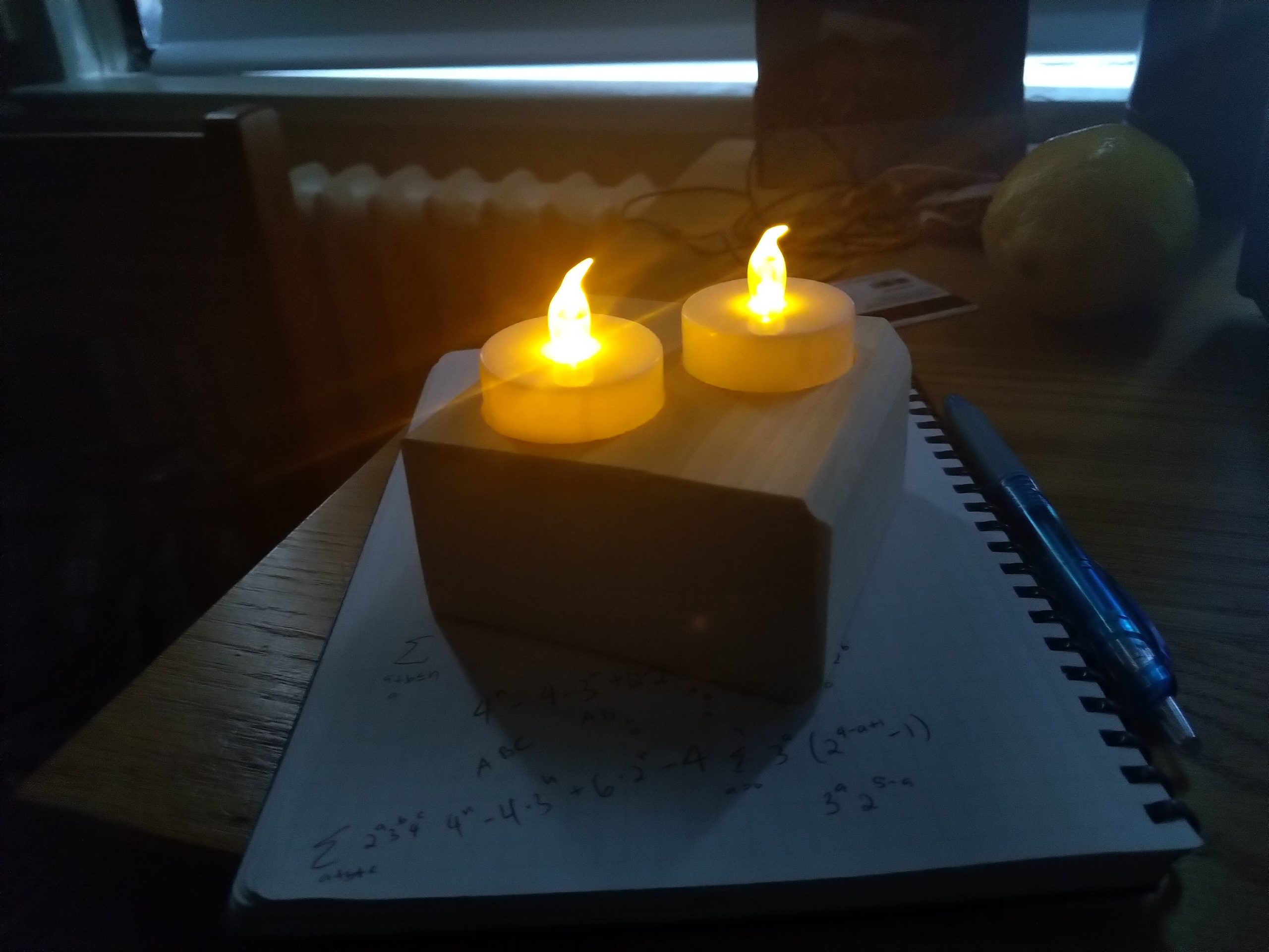 two tea lights on aforementioned tea light holder, on a notebook, in my room, with light peeping in from the not-quite-fully-covered window
