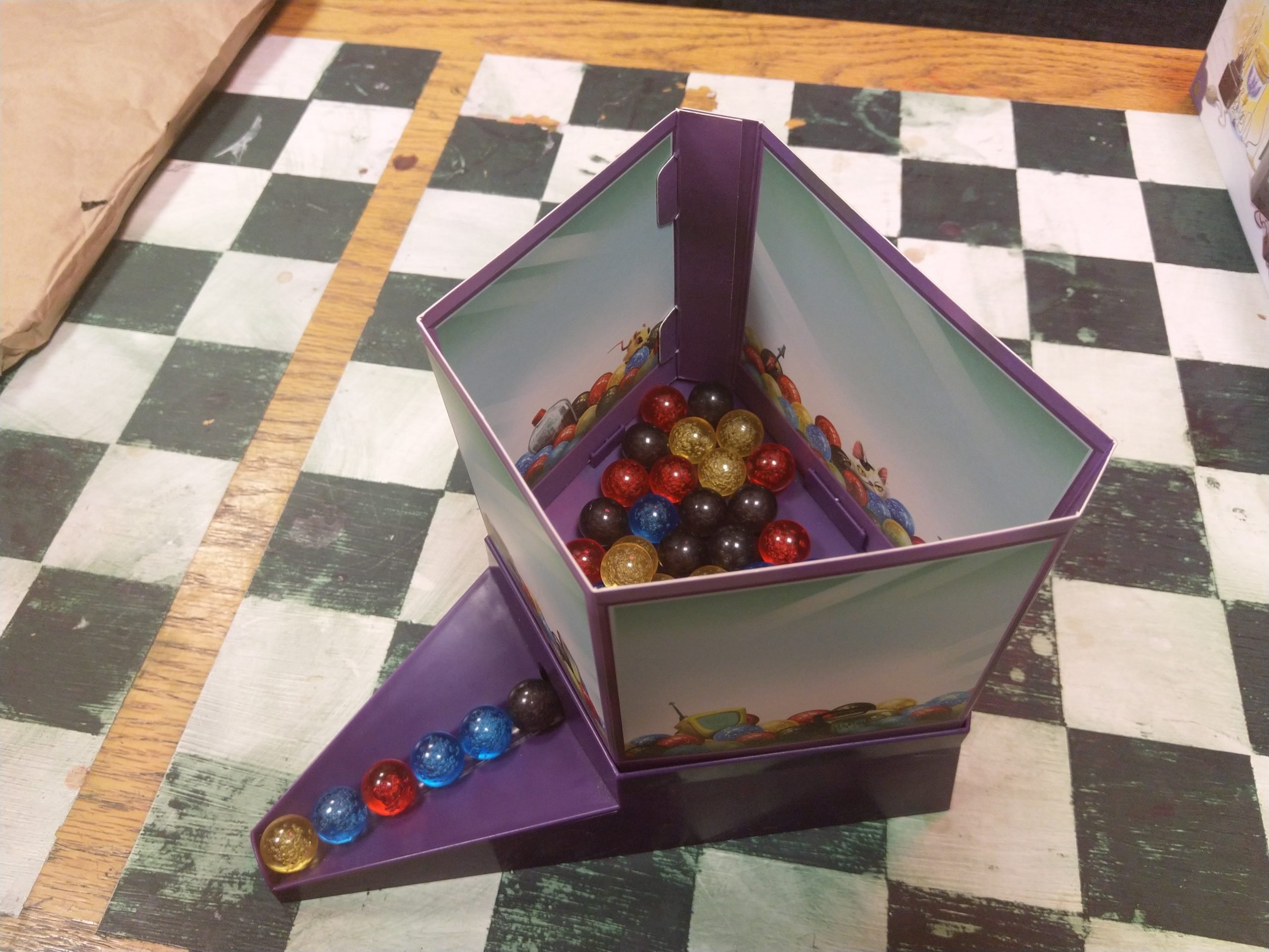 a plastic marble dispenser with marbles of various colors
