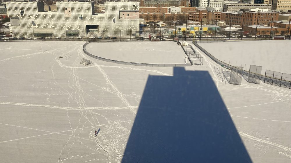 the shadow of my dorm building on a snowy field