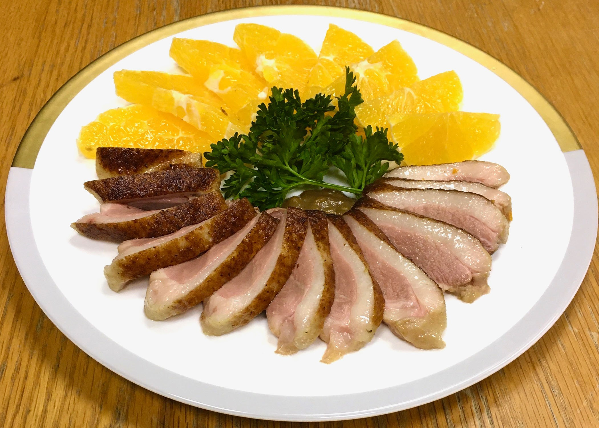 a plate with duck slices and oranges and some sort of vegetable garnish in the middle