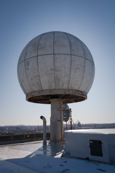 The radome against the sky. It is a white sphere on top of a metal post and ladder.