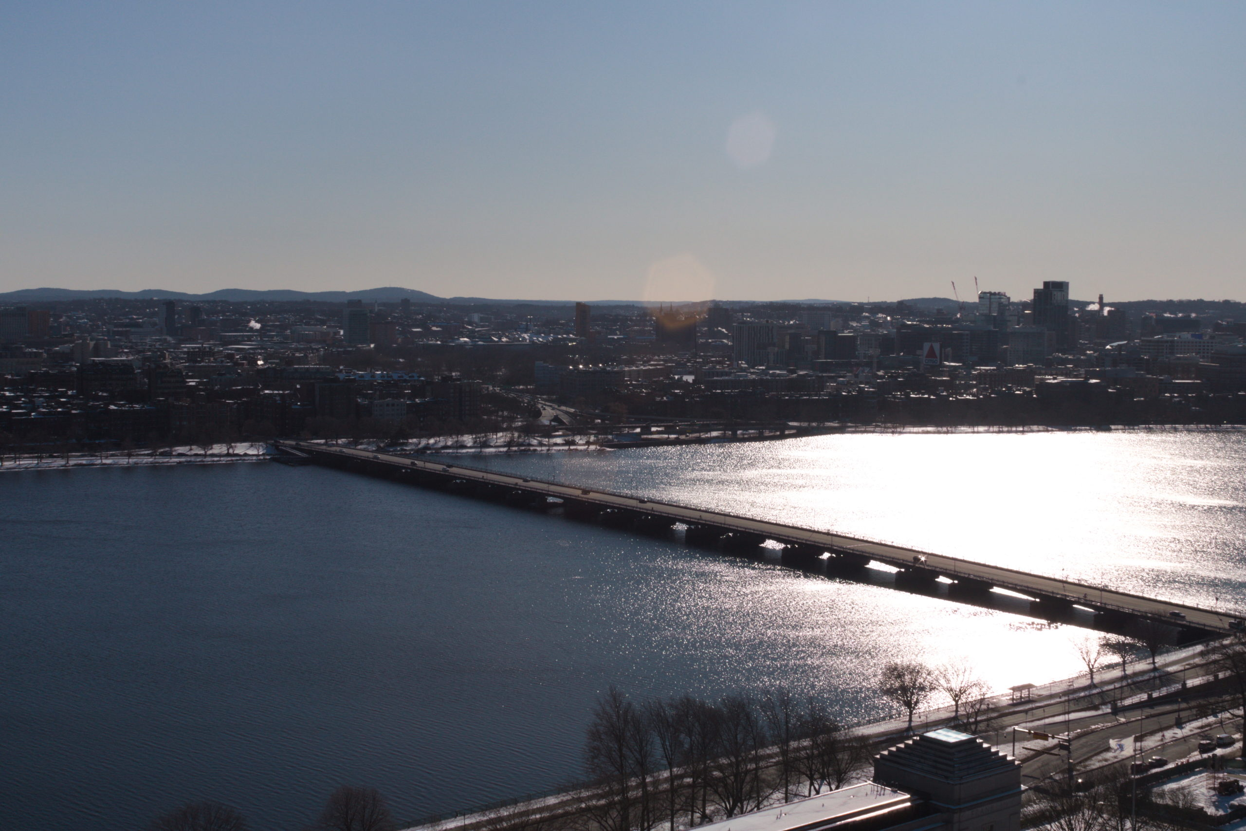 A view from the roof of the Charles River, with the sun glinting off it, and the Harvard Bridge.