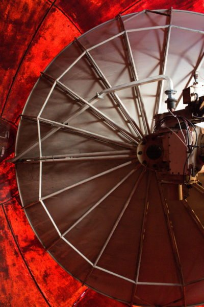 The satellite dish inside the radome. Behind the dish, the light coming through the fibreglass makes it look bright red.