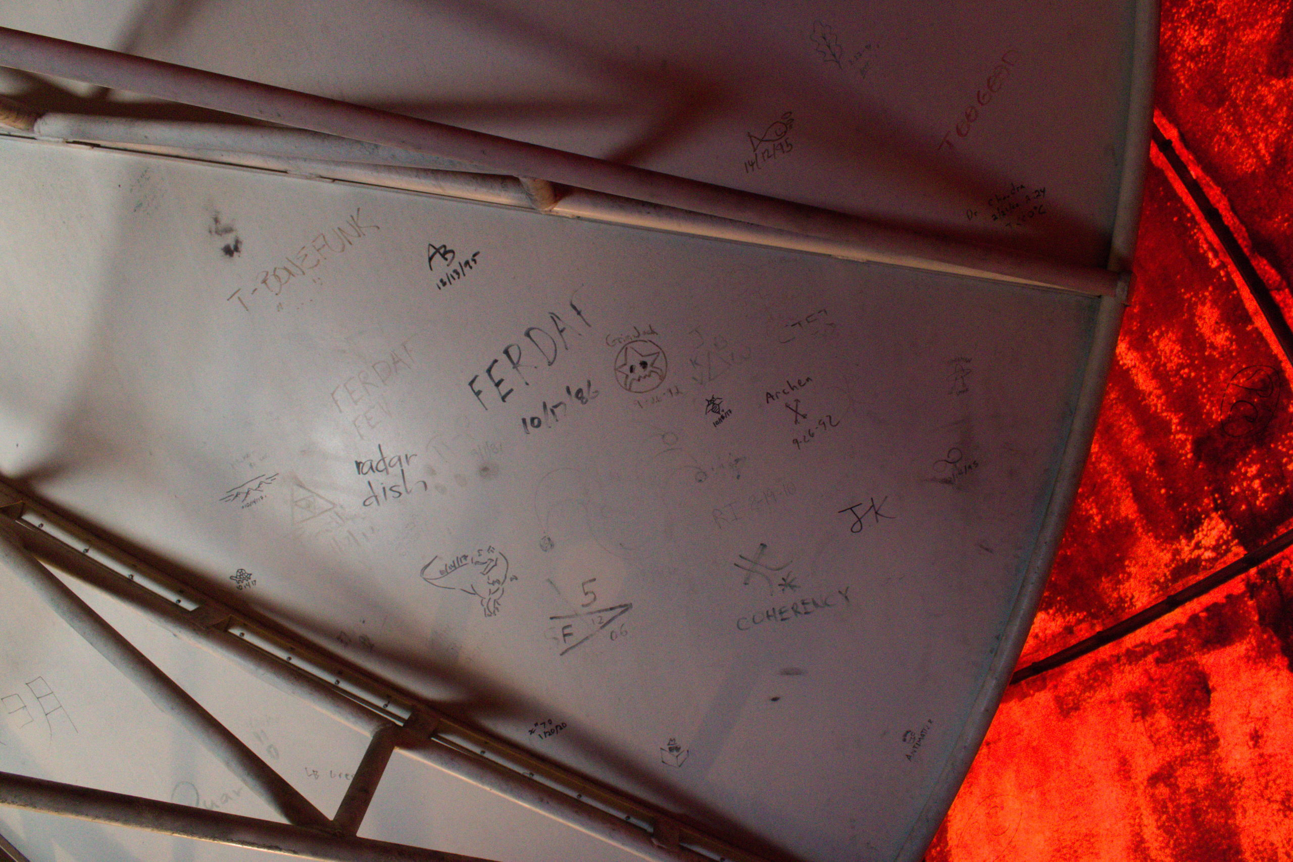 "The back side of the satellite dish. Lots of ""sign-ins"" (nickname signatures and dates) are visible, some as far back as the 80s."