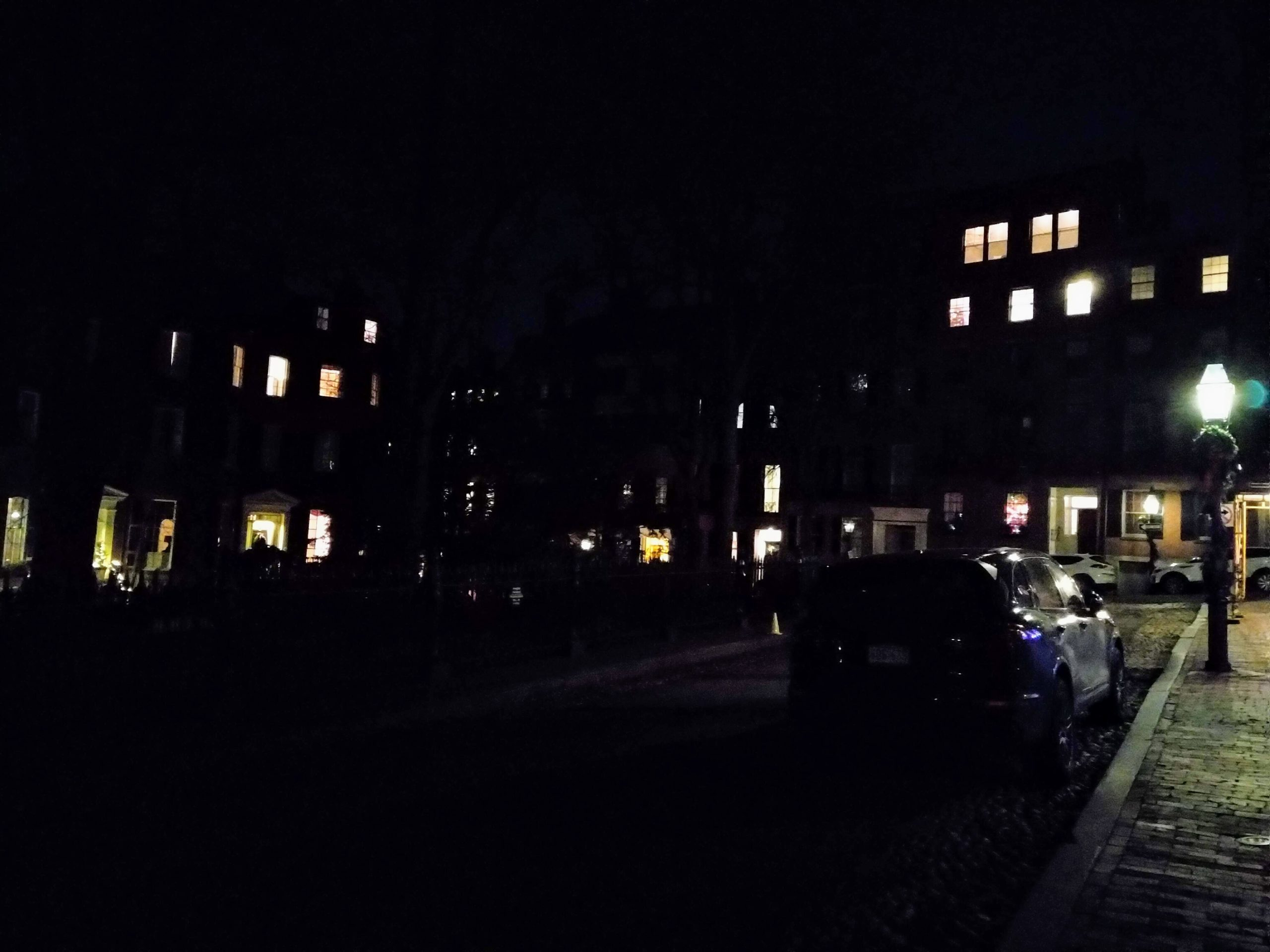 a dimly lit picture of the neighborhood. visible are windows in the distance, a car, and a lamppost.