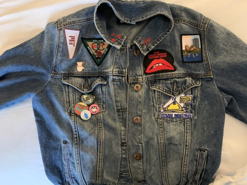a denim jacket with lots of pins and patches, most of which are Boston/MIT-related